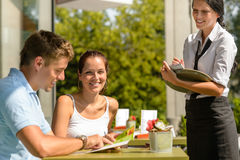 Couple at cafe ordering from menu waitress. Men point menu Stock Photo