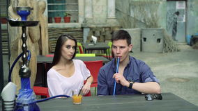 Couple in cafe outdoor: boy smoking, girl looking on him and to camera. 4k stock footage
