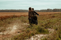 Couple and cafe racer motorcycle. Young, stylish cafe racer couple on the vintage custom motorcycles in a field royalty free stock photo