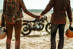 Couple and cafe racer motorcycle. Young, stylish cafe racer couple on the vintage custom motorcycles in a field royalty free stock photos