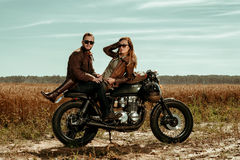Couple and cafe racer motorcycle. Young, stylish cafe racer couple on the vintage custom motorcycles in a field royalty free stock images