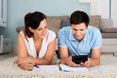 Couple Calculating Bills Together At Home. Happy Couple Lying On Carpet Calculating Bills Together At Home Stock Photo