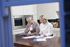 Couple Calculating Domestic Bills At Kitchen Table Stock Image