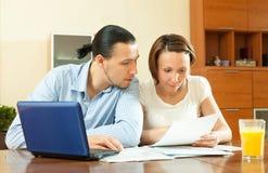 Couple calculating family budge Stock Photos