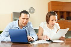 Couple calculating family budget at home Stock Images