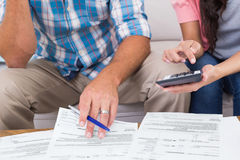 Couple calculating finances at home. Cropped image of couple calculating finances at home Royalty Free Stock Image