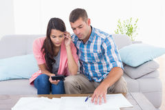 Couple calculating home finances at table. Couple calculating home finances together at table in house Royalty Free Stock Photo