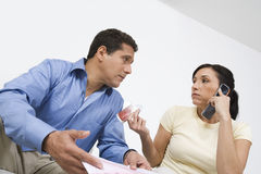 Couple Calling About Credit Card Bill. Worried men with credit card bills looking at women on call Royalty Free Stock Photography