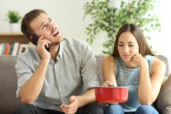 Couple calling insurance for home leaks. Upset couple sitting in a couch in the living room and calling insurance for home leaks stock photo