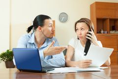 Couple calling by mobile about documents. Couple calling by mobile about financial documents at home interior stock photo