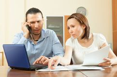 Couple calling by mobile about  documents at home. Adult couple calling by mobile about  documents at home interior Royalty Free Stock Photos