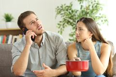 Couple callling to insurance for home leaks. Desperate couple callling to insurance worried about home leaks in the living room royalty free stock image