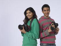 Couple With Cameras In Studio Stock Images