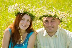Couple in camomile wreaths. Portrait of young couple in camomile wreaths against summer royalty free stock photography