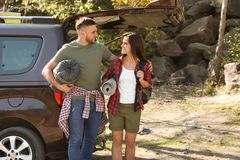 Couple of campers with sleeping bag and mat near car. Outdoors stock photo