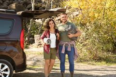 Couple of campers with sleeping bag and mat. Near car outdoors royalty free stock images
