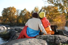Couple of campers in sleeping bags. Sitting on rock royalty free stock photography