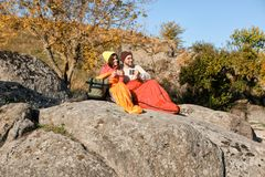 Couple of campers in sleeping bags sitting. On rock royalty free stock images