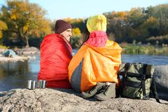 Couple of campers in sleeping bags sitting on rock. Near pond stock images