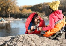 Couple of campers in sleeping bags sitting on rock near pond. Space for text royalty free stock image