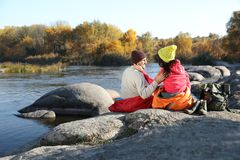 Couple of campers in sleeping bags sitting on rock near pond. Space for text royalty free stock images