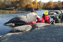 Couple of campers in sleeping bags sitting on rock near pond. Space for text stock images