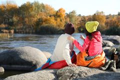 Couple of campers in sleeping bags sitting on rock near pond. Space for text royalty free stock photo