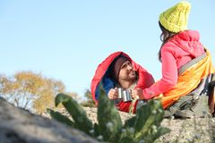 Couple of campers in sleeping bags sitting on rock. Space for text royalty free stock photos