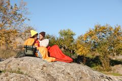 Couple of campers in sleeping bags sitting on rock. Space for text stock photography