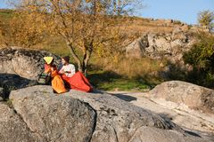 Couple of campers in sleeping bags sitting on rock. Space for text stock image
