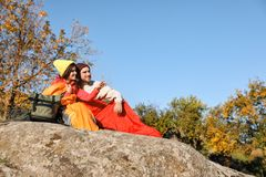 Couple of campers in sleeping bags sitting on rock. Space for text royalty free stock images