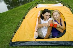 Couple camping. Young couple camping in tent royalty free stock images