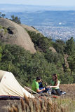 Couple Camping Above the City. Young, attractive couple camping out on a gorgeous summer day with the buildings of the city visible in the background royalty free stock photos