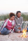 Couple Camping On Beach And Toasting Marshmallows Stock Photos