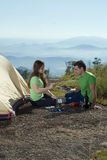 Couple Camping, Cooking With View - Vertical Royalty Free Stock Images