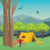 Couple camping in forest man and woman with fire in front of the tent  mountain trees at the background. Couple camping in forest man and woman with fire in Stock Image