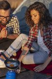 Couple cooking eggs while camping. Couple camping at the lake, cooking eggs for dinner and having fun on an outdoor nature adventure stock photos