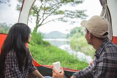 Couple camping by a lake. Portrait of couple camping by a lake, and having a cup of coffee stock photography