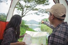 Couple camping by a lake. Portrait of couple camping by a lake and looking at the map stock photography