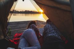 Couple camping on the lake. Young couple in love camping on lake docks, lying on the tent entrance, enjoying beautiful sunset and reading the map in search for royalty free stock photography