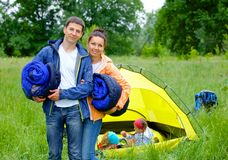 Couple camping in the park. Young happy couple camping near tent in park stock images