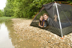Couple camping by a river. Couple in a tent by a river Stock Photos