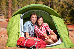 Couple camping in tent happy in romance. Smiling happy outdoors in forest enjoying love looking at view. Happy interracial couple relaxing after outdoor royalty free stock photography