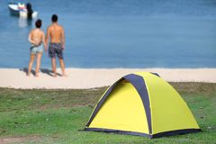 Couple are camping on the white beach with yellow tents. Camping on the white sand beach with green and yellow tents, People or couple are relaxing on the beach Stock Images