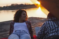 Couple camping. Young couple in love camping on lake docks, lying on the tent entrance, enjoying beautiful sunset and reading the map in search for next royalty free stock photography