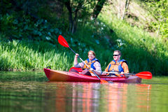 Couple canoe river. Happy men and women canoing on a river Royalty Free Stock Photography