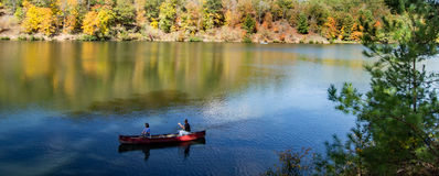 Couple Canoeing on Peaceful Mountain Lake Stock Images