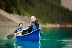 Couple Canoeing and Relaxing. A portrait of a happy woman on a canoeing trip with a man Royalty Free Stock Images