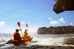 Couple canoeing at sea island backdrop. Couple canoeing or kayaking at sea island backdrop. Krabi province, Thailand. Space for text Royalty Free Stock Image