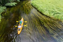 Couple canoeing small slow river in Poland stock photography